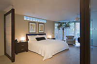 Modern master bedroom seen between wood and frosted glass screens