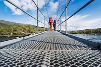 Two hikers cross bridge over river near Abiskojaure hut, Kungsleden trail, Sweden