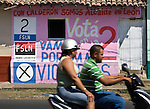 Nicaraguan couple speed past a FSLN headquarters on a moped in Leon, Nicaragua