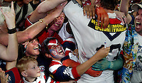 A young fan show his delight as he celebrates with a Sydney Rossters player after their National Rugby League Grand Final win in Sydney, Australia.