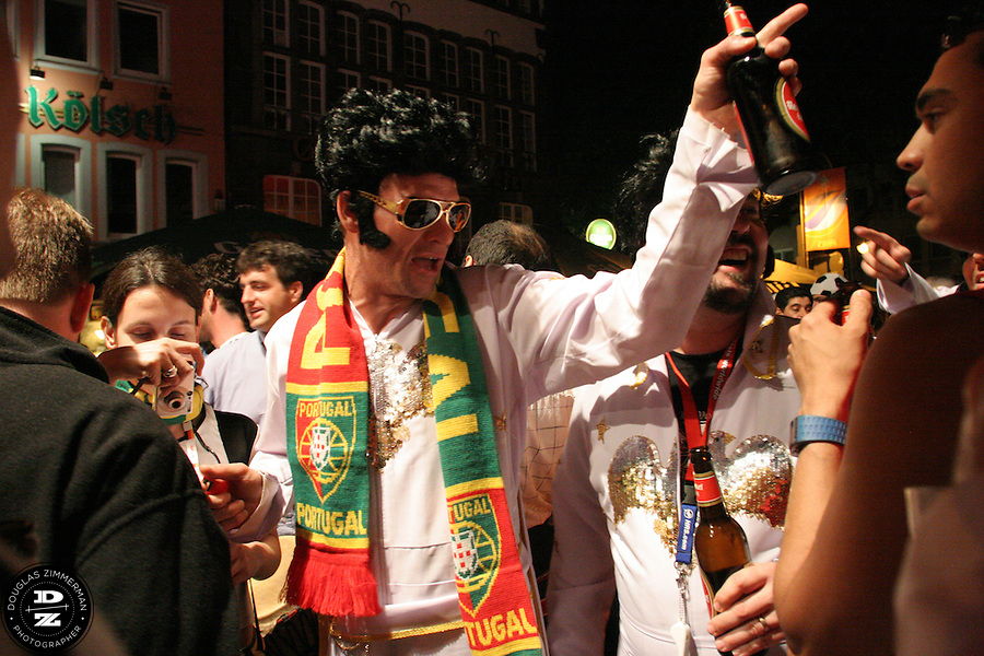 """USA National Soccer Team fan, (left to right) Pat Ryan of Kansas City, MO,  dressed up in flight suits as the American Icon Elvis, enjoys some late night celebrating at a beer garden in Cologne, Germany on Monday, June 12th, 2006  with fans from several other countries.  The fans were part of a tour group arraigned by Pat Ryan from Kansas City, MO called """"2006 World Cup Trip."""" They were among the thousands of American fans who have descended on Germany to support the USA National team during the 2006 FIFA World Cup."""