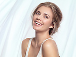 Artistic beauty portrait of a young laughing woman with full smile and clean natural look on white flowy fabric background