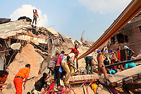 Rescue workers and their helpers look for survivors in the rubble of the collapsed Rana Plaza complex in Savar. The 8 storey building, which housed a number of garment factories employing over 3,000 workers, collapsed on 24 April 2013. By 29 April, at least 380 were known to have died while hundreds remained missing. Workers who were worried about going to work in the building when they noticed cracks in the walls were told not to worry by the building's owner, Mohammed Sohel Rana, who is a member of the ruling Awami League's youth front. He fled his home and tried to escape to neighbouring India after the building collapsed but was caught by police and brought back to Dhaka. Some of the factories working in the Rana Plaza building produce cheap clothes for various European retailers including Primark in the UK and Mango, a Spanish label. . /Felix Features