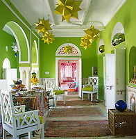 The lime-green wall treatment is based on traditional Indian pigments and the white-painted armchairs in this study/library were made by local craftsmen