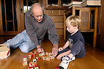 Berkeley CA Boy, four years old, working with puzzle blocks with his grandfather, seventy  MR
