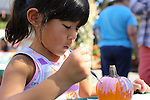 Jolie Cruz, 5, of Sunnyvale paints a pumpkin in the kids' craft area of the Los Altos Fall Festival.