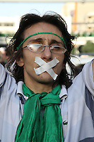 A man in Haftetir Square wearing green, the colour of the opposition, and tape over his mouth as a symbol of his silent protest. Following a disputed election result, thousands of supporters of opposition candidate Mir-Hossein Mousavi took to the streets in protest.