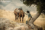 A photo of a cowgirl petting her horse while resting under a tree.