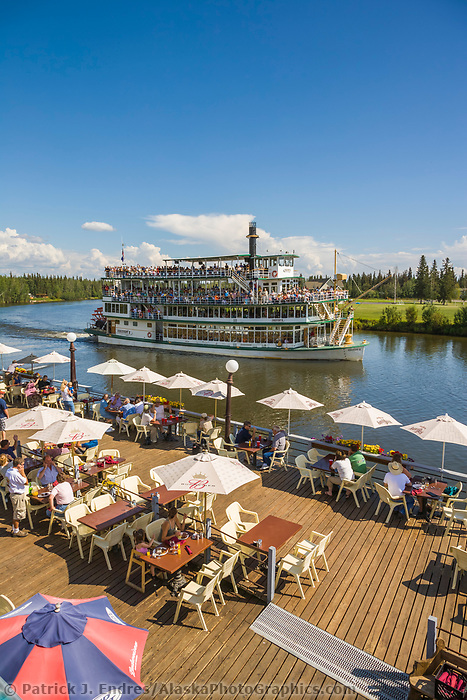 Guests on the deck of the Chena Pump House watch the Riverboat Discovery pass by on the Chena River, Fairbanks, Alaska.