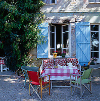 An informal table laid for tea in a shady part of the garden infront of the house