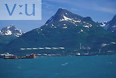 Barge and oil tanker in front of Trans Alaska Pipeline Terminus. Valdez, Alaska