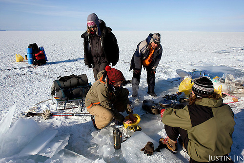 Cooking lunch on the second day trek across frozen Lake Baikal in Siberia, Russia. .They are a group of five people: Justin Jin (Chinese-British), Heleen van Geest (Dutch), Nastya and Misha Martynov (Russian) and their Russian guide Arkady. .They pulled their sledges 80 km across the world's deepest lake, taking a break on Olkhon Island. They slept two nights on the ice in -15c. .Baikal, the world's largest lake by volume, contains one-fifth of the earth's fresh water and plunges to a depth of 1,637 metres..The lake is frozen from November to April, allowing people to cross by cars and lorries.