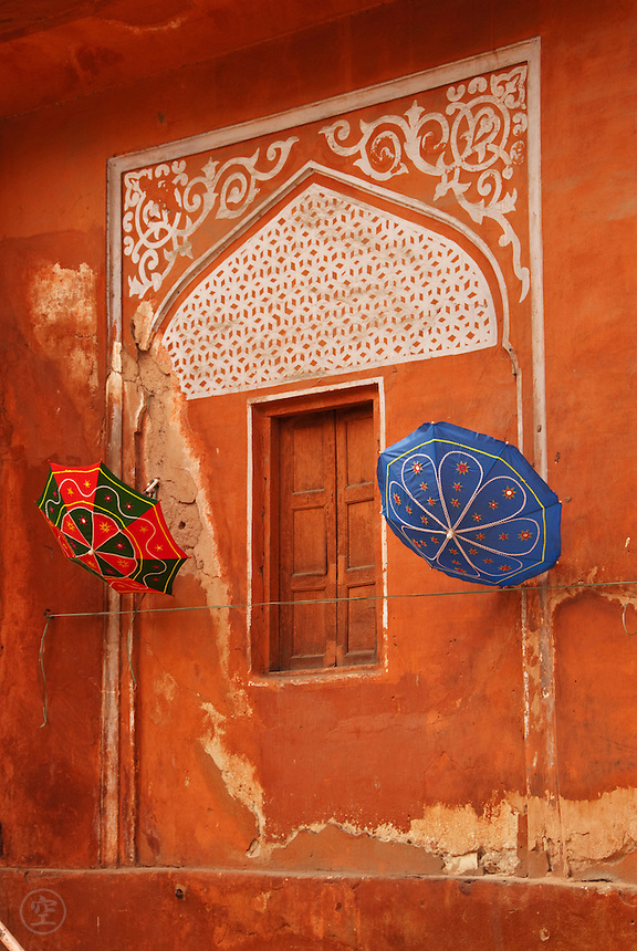 """Colourful umbrellas hang against a decorative window in the terracotta coloured walls of Rajasthan's """"Pink City"""", Jaipur, India."""