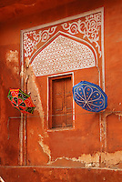 Colourful umbrellas hang against a decorative window in the terracotta coloured walls of Rajasthan's &quot;Pink City&quot;, Jaipur, India.