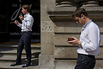 Young City businessmen in matching clothing use smartphones in warm sunshine outside an office building.