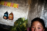 Zhao Min (female, 9, grade 3) stands near her and her brother's backpacks and certificates for good work in school in her family's house in Qingdun Village, Gangyun County, Jiangsu, China.  Zhao Min has lived with her brother Zhao Shi (male, 6) and grandparents Sun Zhan Xia (female) and Zhao Xia You (male) since 2007 when the children were orphaned in 2007. The children's father, Sun Zhan Xia's son, died of hepatitis in 2006 and their mother was forced to remarry and abandon the children in 2007.  Sun Zhan Xia and her husband are both over 60 and in bad health.  The couple owes approximately 40,000 RMB (about $5,300 USD) to pay for the medical treatment of their dead son, the children's father.  Due to their health situation and this enormous debt, the pair cannot afford to care for the children any longer, and the children are in danger of being placed in orphanages.  ..At the time of the picture, China's Amity Foundation charity, was investigating the family's situation in preparation to raise money to financially support these children and other orphans in similar situations.  With Amity's support, each orphan, aged 6-12, would receive approximately 1,400 RMB annually (about 200 USD) to pay for the cost of living. Amity works to keep children out of the institutional orphanages in China, preferring to provide monetary assistance that can help maintain a family environment for the orphans it helps.