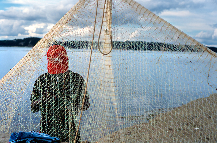 Cigarette pursed in his lips, a recreational fisherman mends his net on a sandbar at the junction of the Rio Negro and Rio Solimões (Amazon) near Manaus, Brazil, Sunday, Jan. 8, 2006. He accused one of the rivers famous pink dolphins of tearing at the net to get at his catch. As the rainy season approaches, the sand playground will disappear under meters of water. (Kevin Moloney for the New York Times)