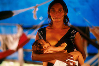 Squatters evicted from occupied estate camp and resist at Brazilian Government Land Institute ( INCRA ) in Marabá city . Community organizing for land reform in East Amazon, Pará State; Brazil. Mother feeding baby.