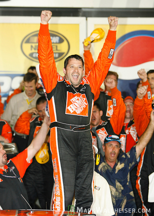 Tony Stewart hops on the roof of his #20 Chevrolet in Victory Lane and celebrates his win in the 2006 Pepsi 400 NASCAR race at Daytona International Speedway in Daytona Beach, Florida July 1, 2006.