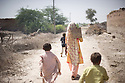 A woman with shuvel and children from her family walk to the men of the household to help recover belongings and clean up the mudd left behind after the floods hit their village. Jamshroo, Pakistan, 2010