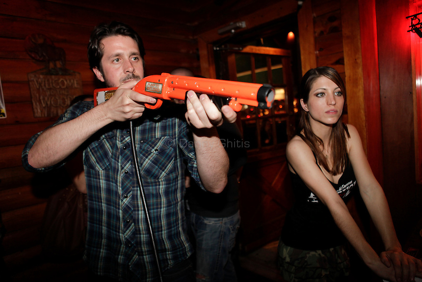 Big Buck Girl Alicia Patterson, 24, right, encourages reigning Big Buck world champion Alex DerHohannesian as he competes at The Black Bear Lodge in Manhattan, which hosted an official Big Buck Party on Thursday April, 28, 2011. Fans of the popular hunting arcade game were invited to test their skill against other Big Buck Hunter fans to compete for prizes, enter to win raffle merchandise and meet Big Buck Girls...Danny Ghitis for The New York Times
