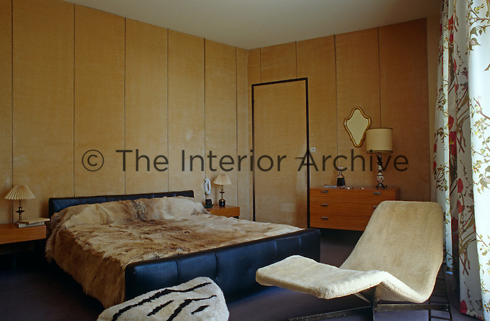 A large double bed with a faux fur cover dominates this 50s style bedroom