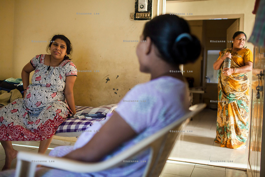 9 months pregnant, Leela Mekwan (left), 34, chats with other surrogates as they while their time away in the surrogates hostel on the 3rd floor of Dr. Nayana Patel's Akanksha IVF and surrogacy center in Anand, Gujarat, India on 10th December 2012. Photo by Suzanne Lee / Marie-Claire France