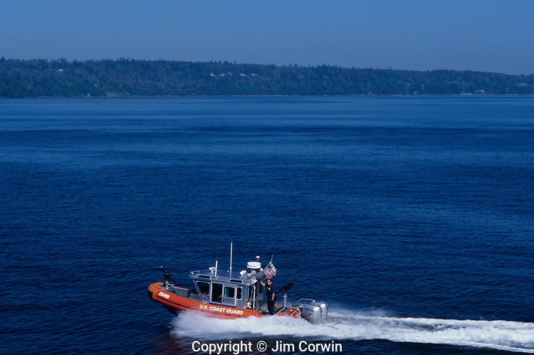 Ferry boat crossing waterway Puget Sound and Olympic Mountains on a sunny day with coast guard escort Seattle Washington State USA.