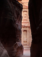 Siq leading to Treasury of the Pharaohs, Petra, Ma'an, Jordan. The Siq is a 1.2km gorge formed when the earth split by tectonic forces and is the main entrance to Petra. The Treasury of the Pharaohs or Khazneh Firaoun, 100 BC - 200 AD, was originally built as a royal tomb and is so called after a belief that pirates hid their treasure in an urn held here. Carved into the rock face opposite the end of the Siq, the 40m high treasury has a Hellenistic facade with three bare inner rooms. Petra was the capital and royal city of the Nabateans, Arabic desert nomads. Picture by Manuel Cohen