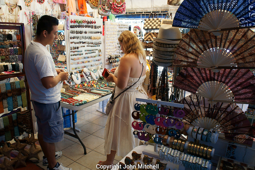 Woman tourist making a purchase in Mercado 28 souvenirs and handicrafts market in  Cancun, Mexico      .