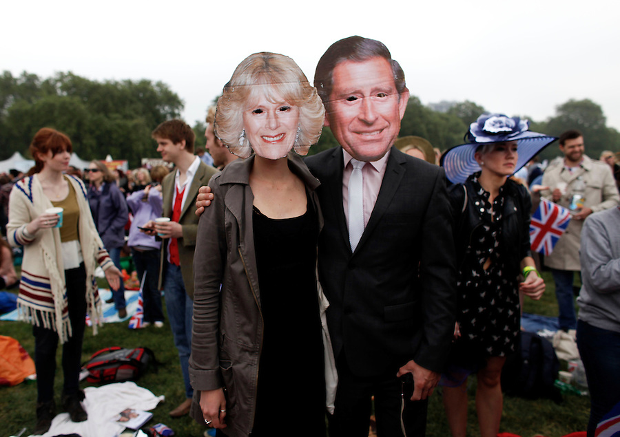 Royal enthusiasts wear Prince Charles and Camilla, Duchess of Cornwall masks at a public viewing of the Royal wedding of Prince William and Kate Middleton in Hyde Park.