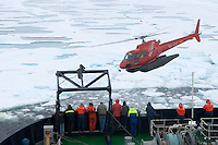 Scientists and technicians watching a helicopter from an icebreaker research vessel trying to retrieve an unmanned scientific submersible trapped in the Arctic Ocean ice below.