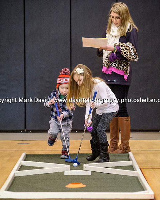 Could be hockey or it could be a new kind of team golf. Logan and Alivia Dylo team up on getting their ball in the hole watched by their mother, Rebecca. The fourth annual 4th Altoona Elementary Golf in the Halls was held Jan. 28. Participants enjoyed a breakfast and  two, 18-hole mini-golf courses throughout the school's classrooms, hallways and gymnasiums.