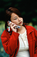 China. Shanghai. Downtown. City center. Young woman uses a portable phone in the streets. © 2002 Didier Ruef