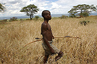 Yaeda Valley, Tanzania: Ngaola, a Hadzabe man, walks through the grasses in front of his family's settlement (in the distance) in Northern Tanzania. He still hunts with poison arrows almost every day, though for various reasons large game is more scarce these days than it once was. The Hadzabe are the second oldest people on earth, according to DNA testing, which traces their origins to 90,000 years ago, or shortly after human evolution. They are one of the last remaining tribes of hunter gatherers on earth. (PHOTO:  MIGUEL JUAREZ LUGO)