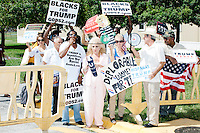 "A group of men led by a man calling himself ""Michael the Blackman,"" 57, of Miami, (with bullhorn) holding signs reading ""Blacks for Trump"" joined a small group of pro-Trump protesters gathered outside a campaign rally for Democratic presidential nominee Hillary Clinton in the Theodore R. Gibson Health Center at Miami Dade College-Kendall Campus in Miami, Florida, USA. The protesters shouted hateful language to people lined up to enter the rally."