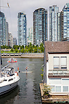 The view of Vancouver, British Columbia from Granville Island over False Creek. A woman on a SUP (Stand Up Paddleboard), paddles by the water houses.