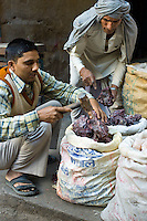 Rock salt being chopped for sale at Khari Baoli spice and dried foods market, Old Delhi, India
