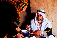 A Kurdish woman serves tea to an Arab man. Harran, Turkey.