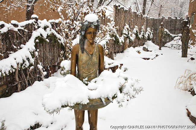 A bronze sculpture of a flower girl takes on a romantic air  during a winter snowfall on Canyon Road in Santa Fe, New Mexico