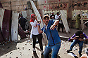 A female protester helps move a metal shield to aid a mix of Salafi and revolutionary youth activists in a rock throwing battle with Egyptian security forces during intense May 4, 2012 demonstrations against the ruling Supreme Council of the Armed Forces (SCAF) near the Defense ministry building in the Abbasiya district of Cairo. Close to 300 people were injured in the clashes, one killed, and an estimated 300 people arrested by the military.