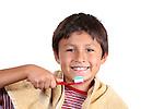 Young boy brushing teeth on white background