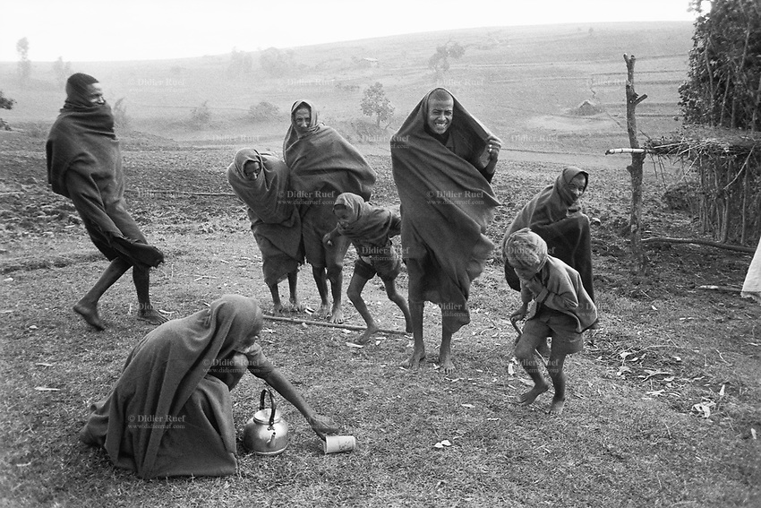 Ethiopia. West Gujam. Danbecha district. Anjeni is a small village. A group of men, surprised by a sudden rainfall storm while preparing tea, cover their heads with loinclothes. © 1996 Didier Ruef