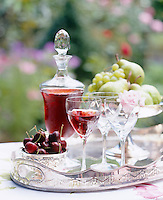Detail of a silver tray with a bowl of fresh cherries, a decanter of wine and glasses