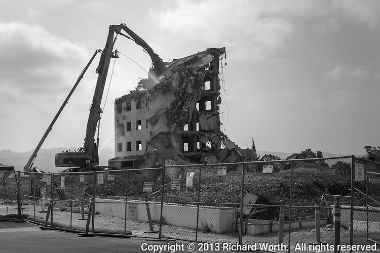 Demolition in progress on the former Eden Hospital in Castro Valley, California.  Rendered in black and white, this image accentuates the empty windows with gray sky showing through.