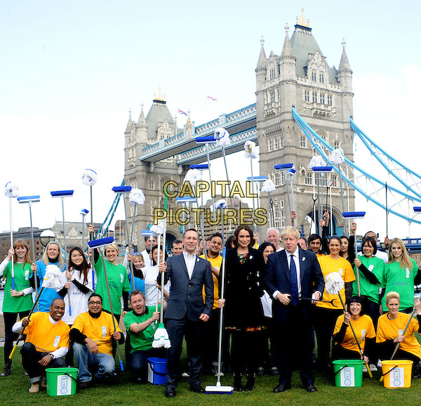 Mayor Boris Johnson & Keeley Hawes .The P&G Capital Clean Up launch campaign photocall, Potters Field Park, London, England..March 8th, 2012.full length black jacket suit blue tights coat bow ankle boots  broom MP  crowd cleaners brooms .CAP/WIZ.© Wizard/Capital Pictures.
