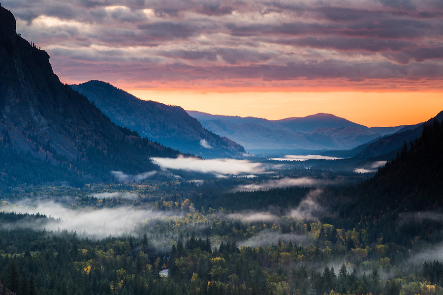 The rising sun colors the clouds magenta and pink as pockets of fog swirl below in a valley below Hart's Pass, Washington State.