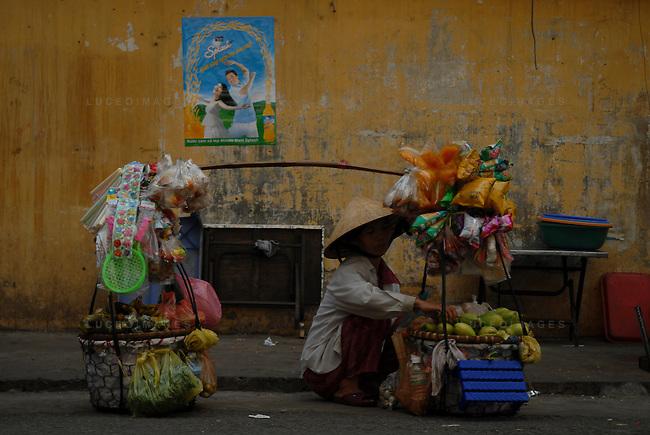 A woman sells goods on the side of the street in Ho Chi Minh City, Vietnam.