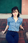 Brunette sitting on the curb waiting, wearing blue denim shirt