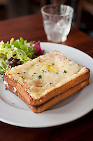 A croque-monsieur ham and cheese sandwich at a French cafe.